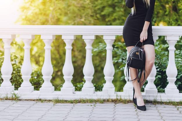 Женщина позирует на улице, держа темную сумку