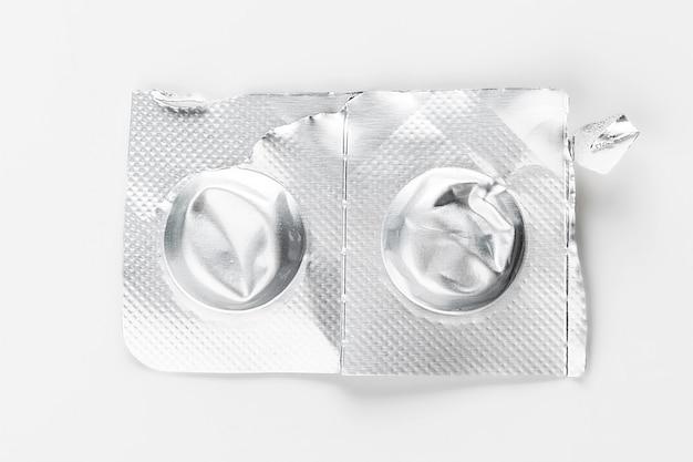 白で隔離される銀のブリスターパックの丸薬