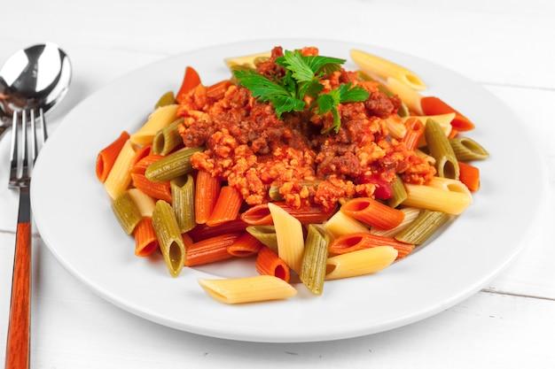 テーブルの上の肉、トマトソース、野菜のパスタ