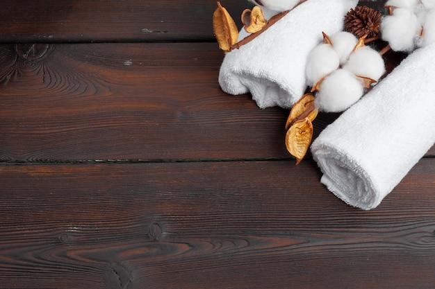 Хлопковые цветы с полотенцем на деревянном столе