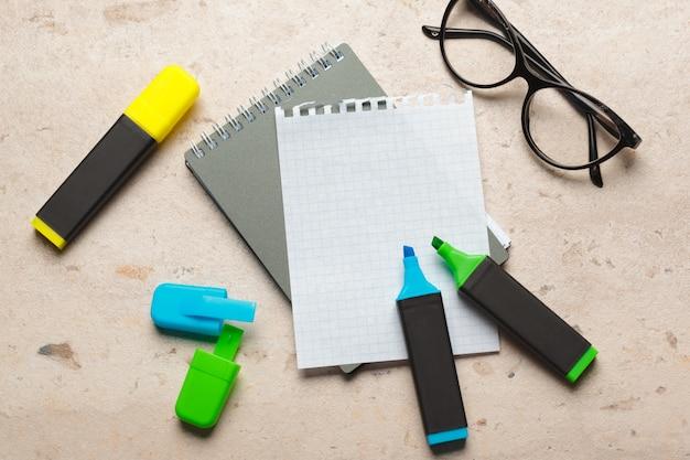 空白のメモ帳用紙フラットの青と緑の蛍光ペンは机の上に横たわっていた