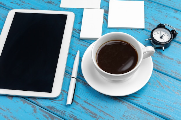 青い机の上の文房具のブランディング。紙、名刺、パッド、ペン、コーヒーの平面図。