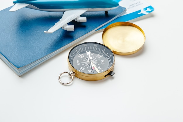 Время путешествовать. идея туризма с авиабилетами и компасом на белом