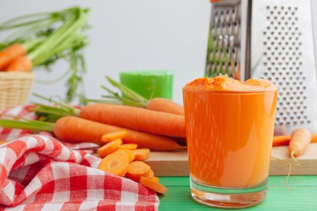 Очки морковного сока с овощами на столе крупным планом