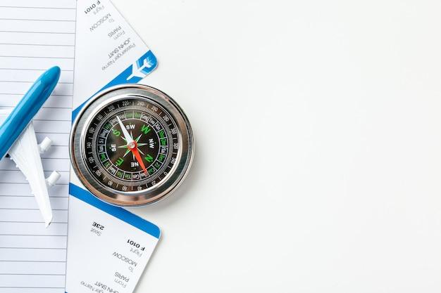 Время путешествовать. идея для туризма с авиабилетами и компасом на белом фоне