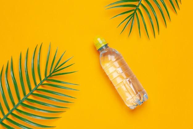 Прозрачная жидкая бутылка с тропическими пальмовыми листьями, вид сверху
