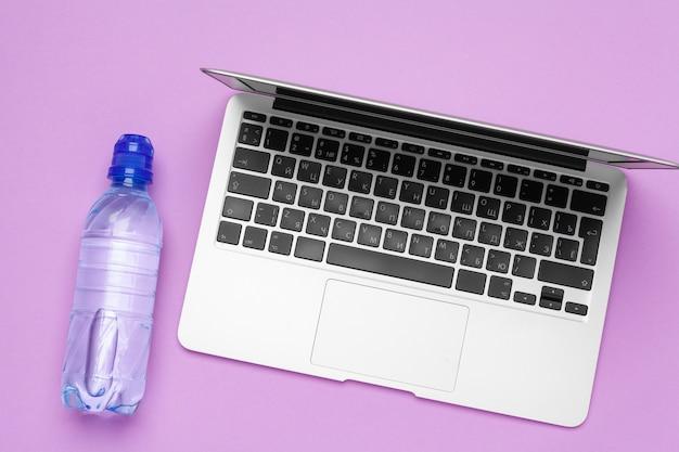 ノートパソコンの近くのオフィスのテーブルの上の水のボトル