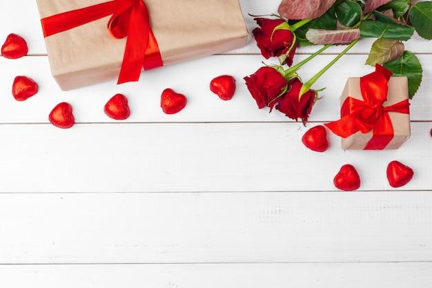 聖バレンタインデーの背景。赤いバラと木製のテーブルの上のギフトボックス