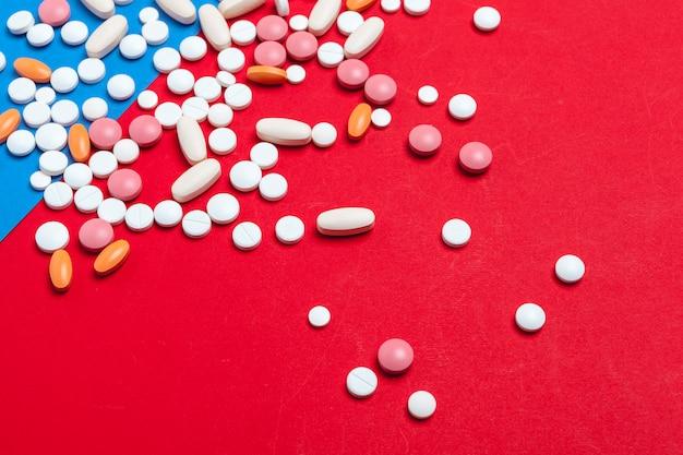青と赤の色とりどりの丸薬。医療テクスチャ。