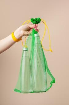 Сетчатые пакеты с многоразовой стеклянной бутылкой для воды. устойчивый образ жизни. ноль отходов концепции.