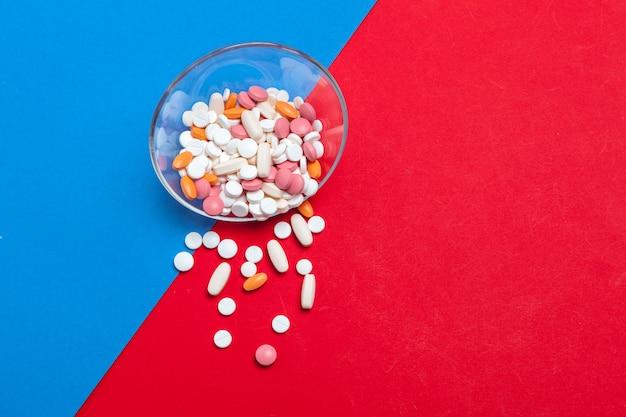 青と赤の色とりどりの丸薬。医療コンセプト。テクスチャ。