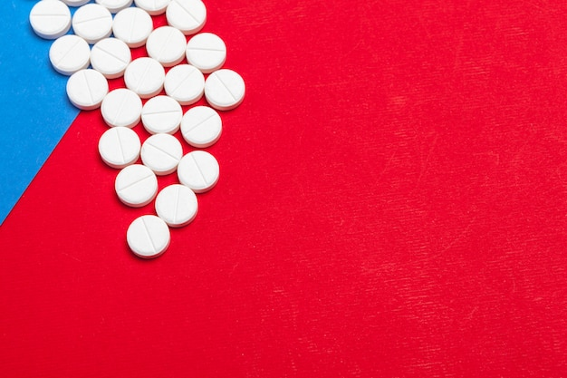 Белые медицинские таблетки на двухцветном красном и синем фоне