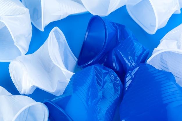 使い捨ての色のプラスチックカップのゴミ。ゴミと汚染の概念
