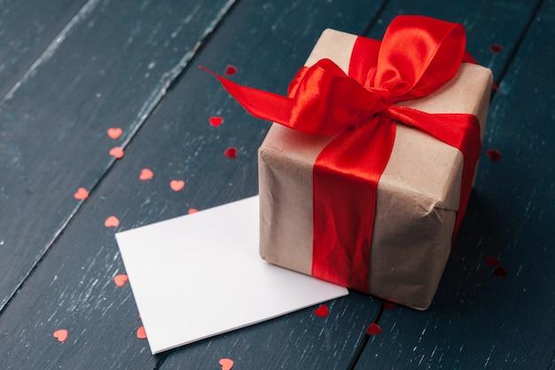 Подарочная коробка с красными сердцами на деревянный стол