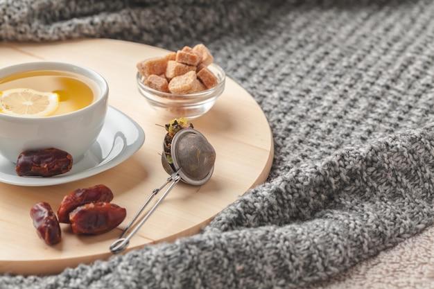 Вид сверху на чашку чая с кусочком лимона на деревянном столе