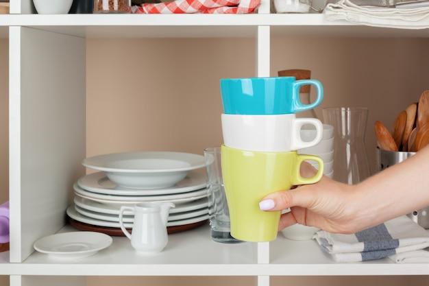 Рука женщины, принимая куски посуды с полки на кухне