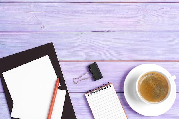 木製の机の上のコーヒーカップでノートブックを開く