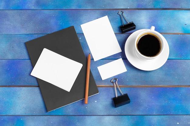 モックアップチェックリスト、青い木のコーヒーカップと空のメモ用紙。オフィス、作家、研究