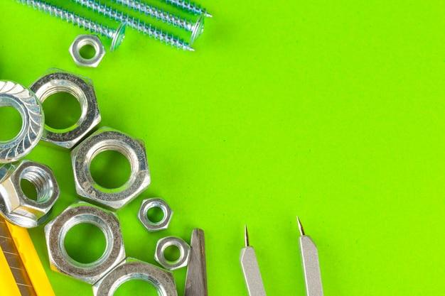 エンジニアリングツール。緑色の背景でボルトとナット