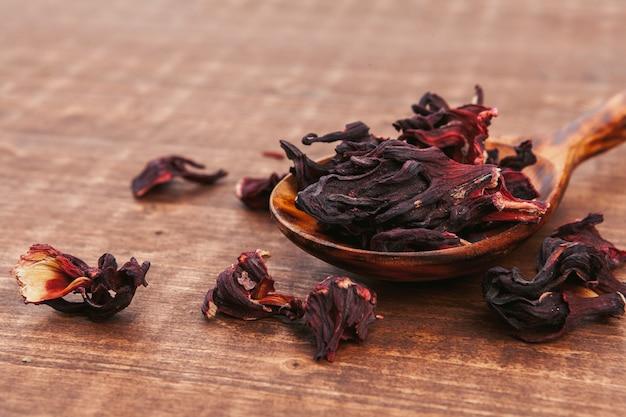 木の板に木製のスプーンでハーブと紅茶