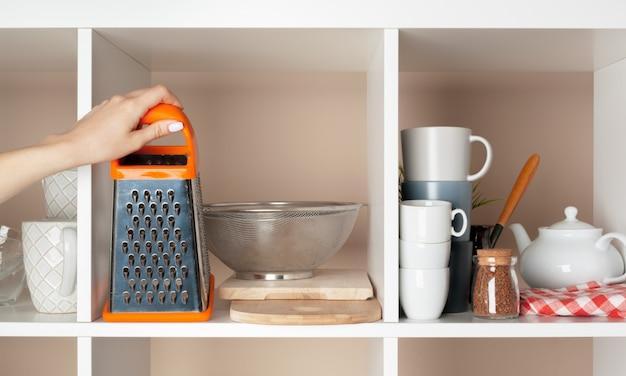 台所の棚から食器片を取る女性の手