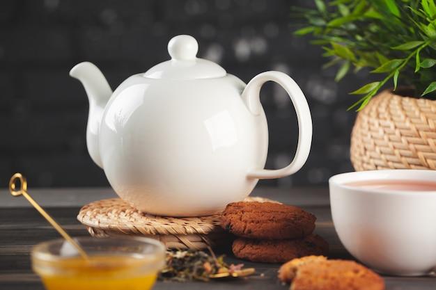 木製のテーブルに紅茶のカップとガラスのティーポット