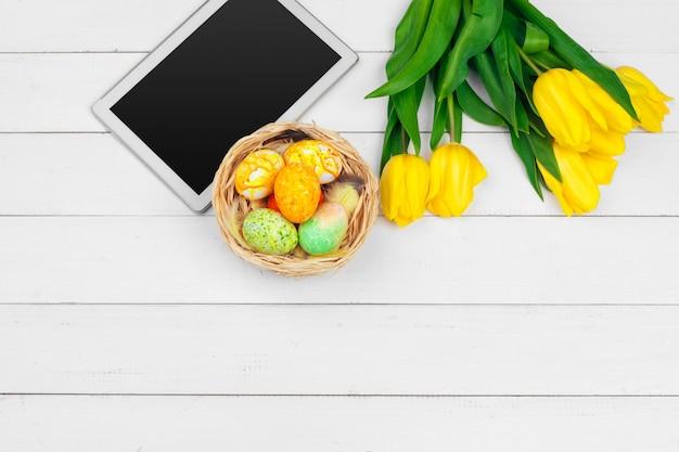 Экран планшета для сообщений и разноцветных тюльпанов и пасхальных яиц