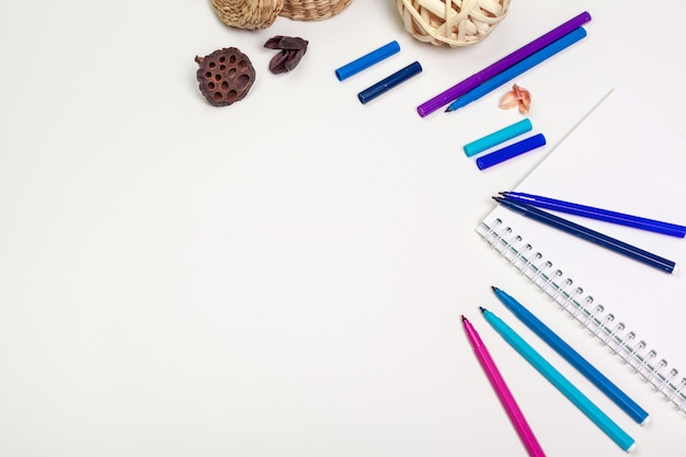 白いテーブルにスパイラルメモ帳の空白ページ。クレヨン鉛筆とペンフラットレイアウト写真。テーブルトップビューの空のスケッチブックページ。
