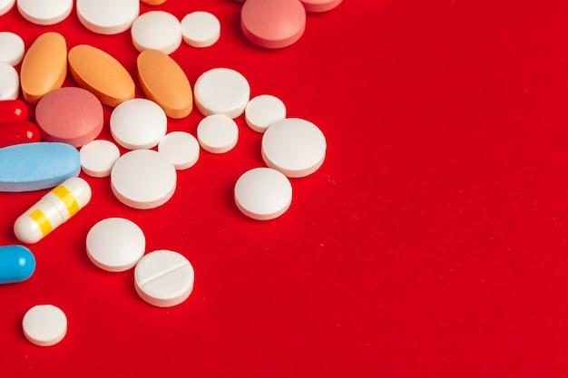Многие таблетки крупным планом на красный