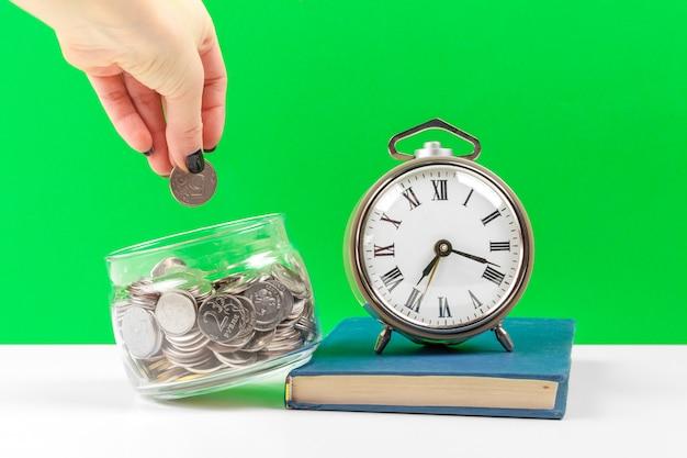 Будильник и деньги монеты на столе.
