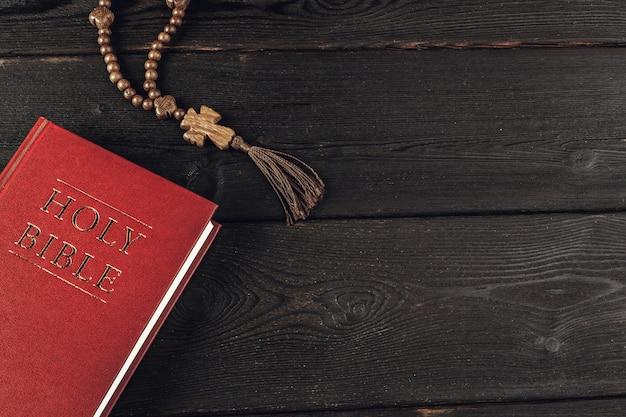 Библия и распятие на старом деревянном столе. концепция религии