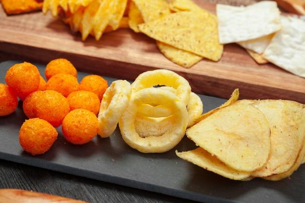 Микс закусок: крендели, крекеры, чипсы и начос на столе