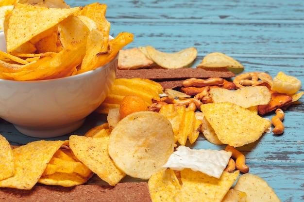Пивные закуски, такие как крекеры, чипсы, печенье на деревянной поверхности