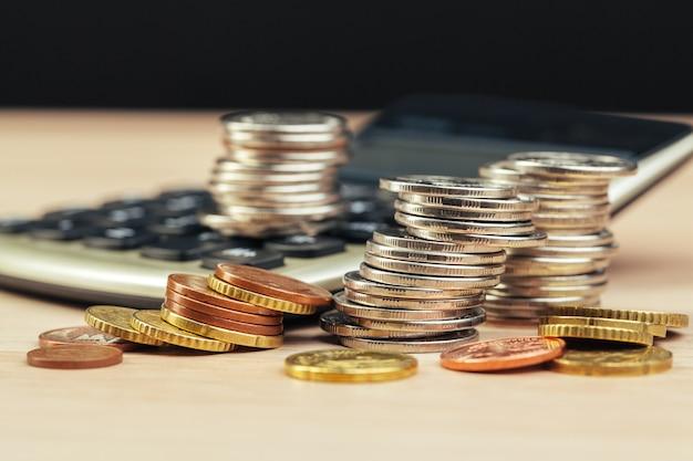 コインと電卓のスタック、ビジネスファイナンスのコンセプトアイデア
