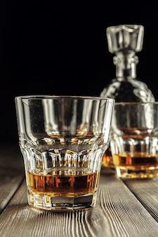 ウイスキーグラスとボトルの古い木製のテーブル