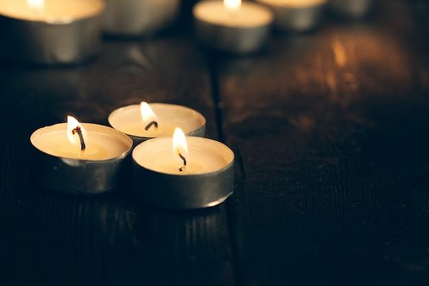 暗闇の中で燃えているキャンドル。記念コンセプト。