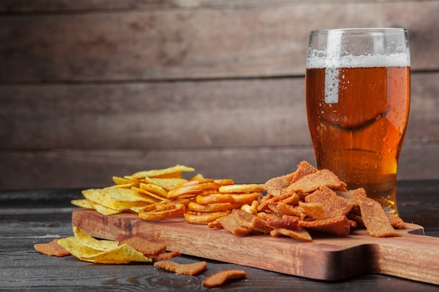 ラガービールと木製のテーブルのスナック。ナッツ、チップ、プレッツェル