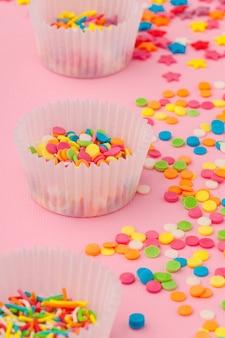 Сахар окропляет еду на розовом картоне