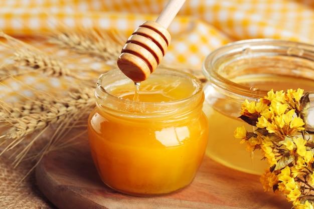 はちみつ 。木製の背景にガラスの瓶に甘い蜂蜜。