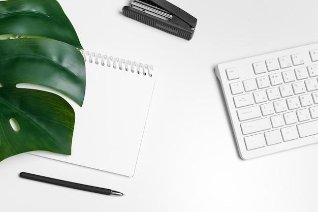コンピューターのキーボードと消耗品のモダンな白いオフィスデスクテーブル。トップビュー、フラットレイアウト。
