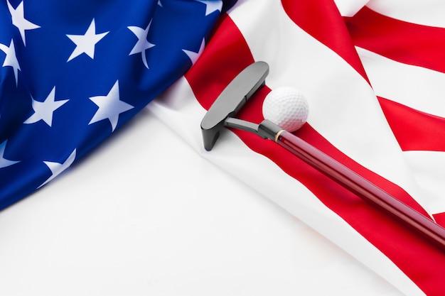 ゴルフボールとアメリカの国旗のクラブ。