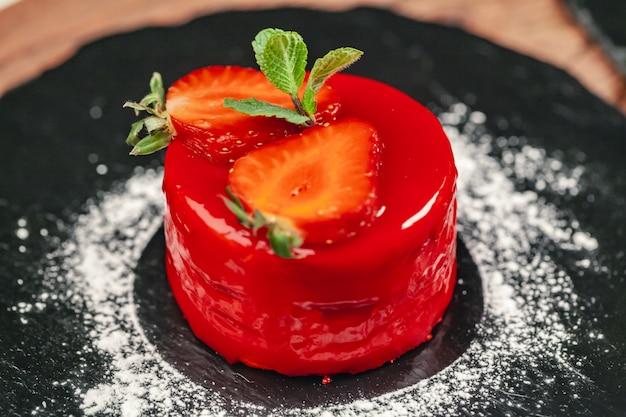木製テーブルの上の白い皿にクリームと赤いケーキ
