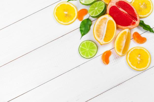 白い木製の背景に柑橘系の果物の明るい組成