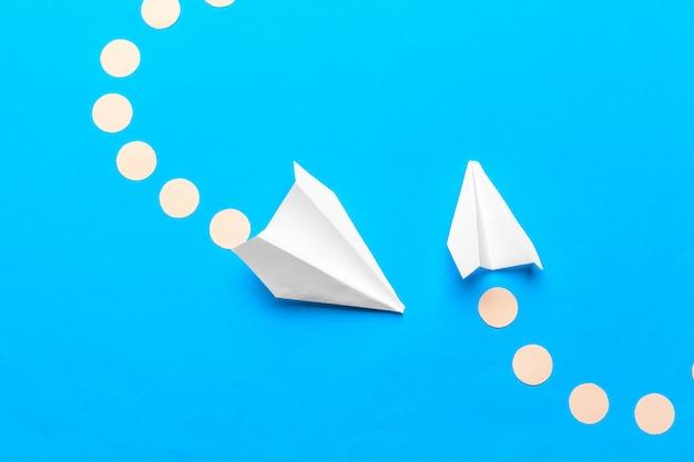 パステルブルーの色に白い紙飛行機と白紙のフラットレイアウト