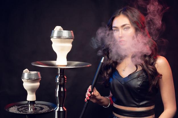 黒のドレスで若い美しい女性喫煙と水ギセルを吐き出す