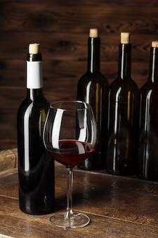ボトルと暗い木製の木製の樽に赤ワインのグラス