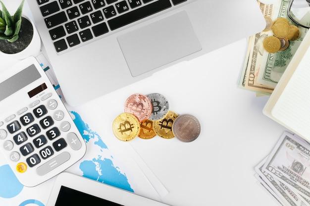 Ноутбук на столе возле долларов и биткойнов в офисе