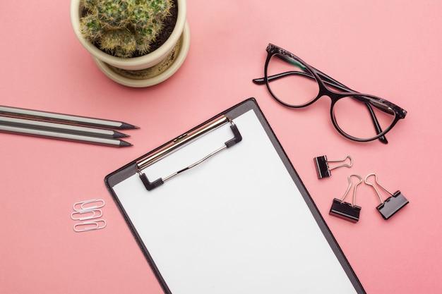 ピンクのパステルに空のクリップボード紙