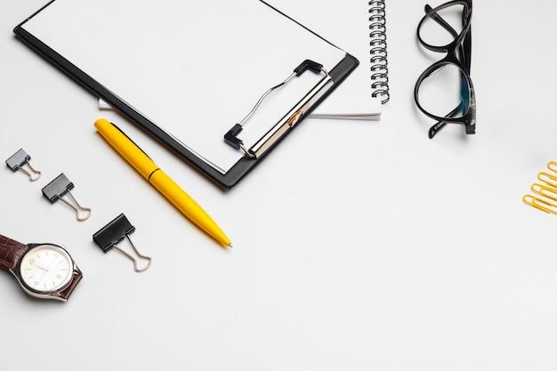 白いシートと白い背景で隔離のペンを使用してクリップボード。上面図