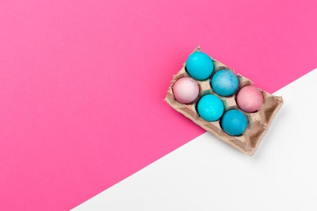 ピンクの紙の背景の上のキャンディー色のイースターエッグ